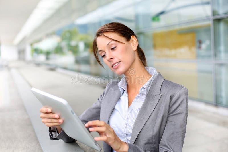 Affärskvinna genom att använda tableten fotografering för bildbyråer