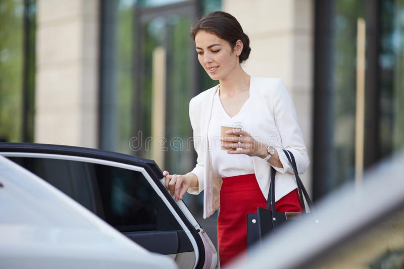 Affärskvinna Getting in i bilen arkivbild