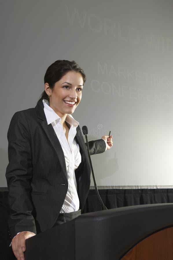 Affärskvinna Giving en föreläsning på podiet royaltyfria bilder