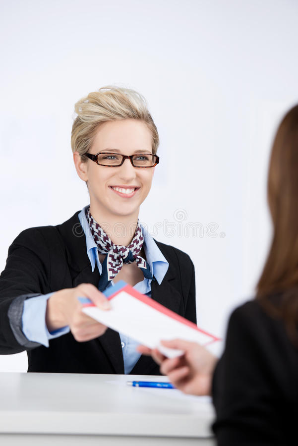 Affärskvinna Giving Traveling Documents till receptionisten arkivfoto