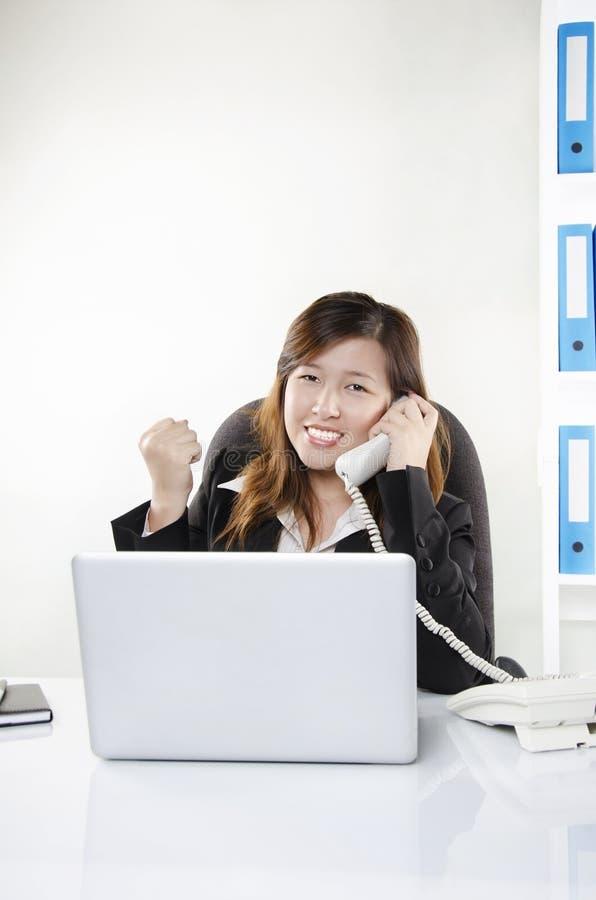 Affärskvinna glädjande på telefonen arkivfoto