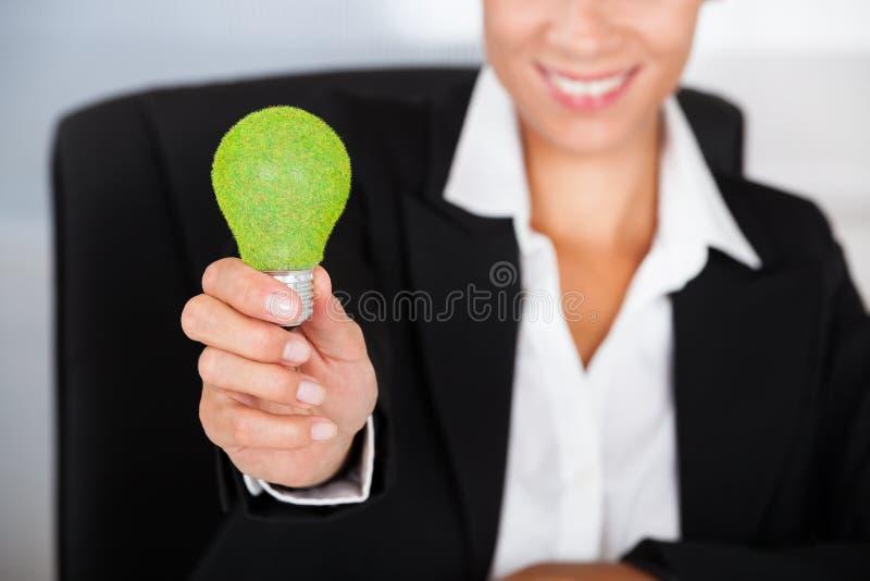 Affärskvinna With Green Bulb arkivfoton