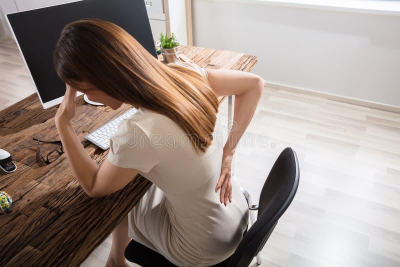 Affärskvinna Having Back Pain på arbetsplatsen arkivbild