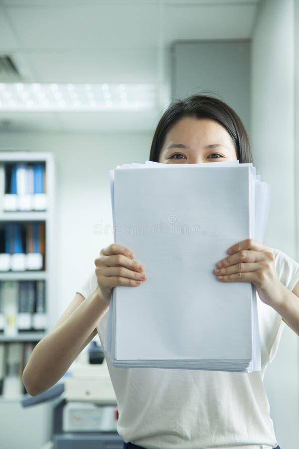 Affärskvinna Hiding Behind Paper royaltyfri bild