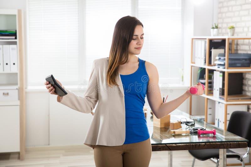 Affärskvinna Holding Calculator Exercising med hantlar royaltyfria foton