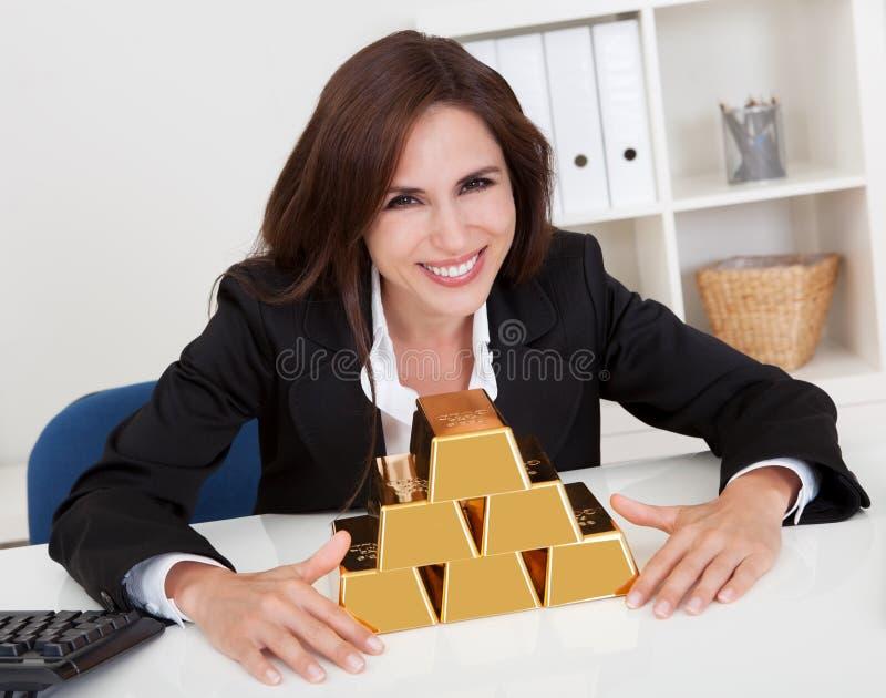 Affärskvinna Holding Gold Bar fotografering för bildbyråer