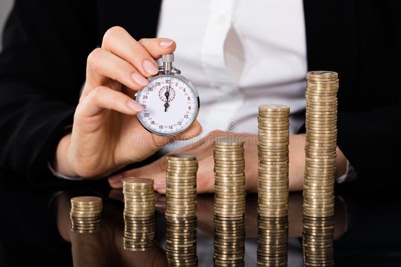Affärskvinna Holding Stopwatch In Front Of Stacked Coin royaltyfri fotografi
