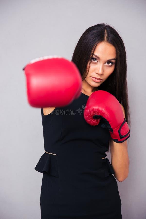 Affärskvinna i boxninghandskar som stansar på kameran royaltyfri bild