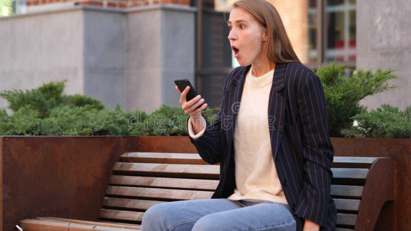 Affärskvinna i chock som reagerar till resultat på Smartphone fotografering för bildbyråer