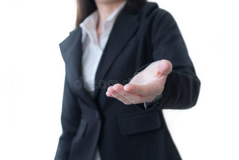 Affärskvinna i den öppna handen för svart dräkt för show något på vit bakgrund arkivbild