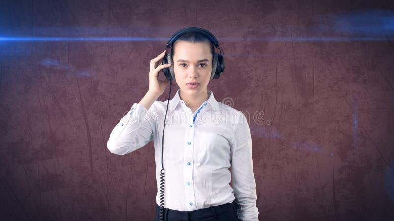 Affärskvinna i den vita kjolen som kopplar av att lyssna till musik på stereo- hörlurar med lycksaligt leende Isolerad bakgrund royaltyfria bilder