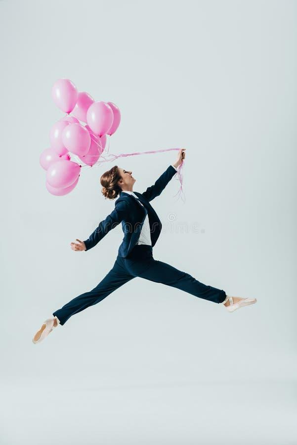 affärskvinna i dräkt- och balettskor som hoppar med rosa ballonger royaltyfria foton