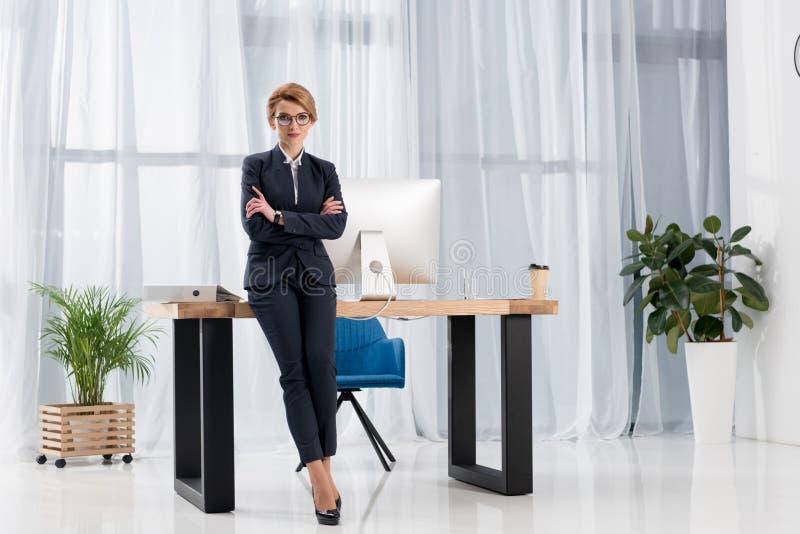 affärskvinna i dräkt och glasögon som lutar på tabellen arkivfoto