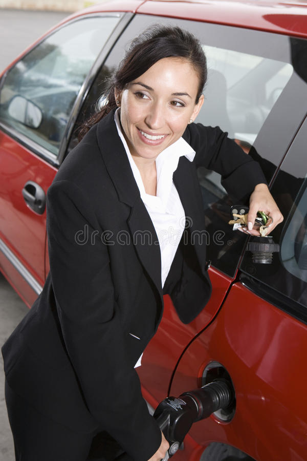 Affärskvinna i dräkt som tankar hennes röda bil royaltyfri fotografi