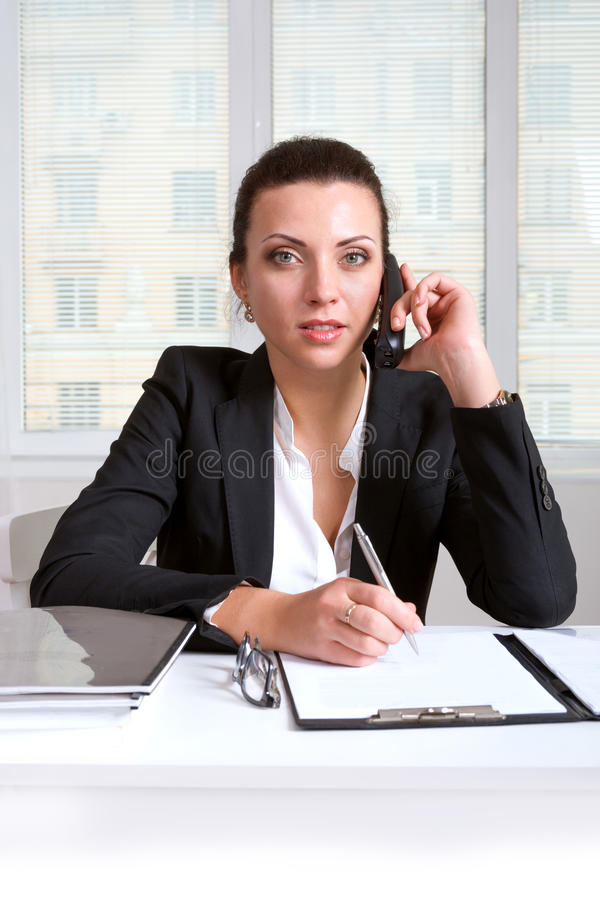 Affärskvinna i en dräkt som talar på en telefon royaltyfri fotografi