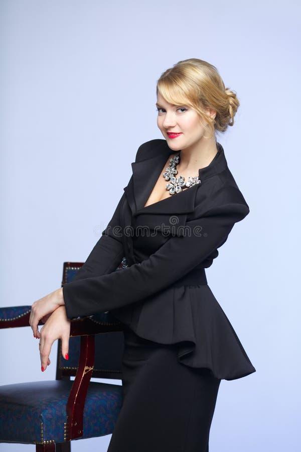 Affärskvinna i en elegant svart dräkt arkivfoton