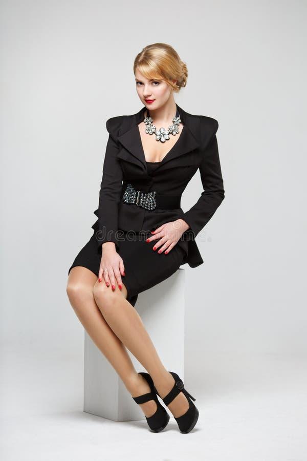 Affärskvinna i ett elegant svart dräktsammanträde på en vit kub royaltyfri foto
