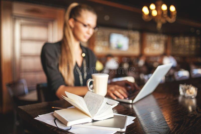 Affärskvinna i exponeringsglas inomhus med kaffe och bärbara datorn som tar anmärkningar i restaurang fotografering för bildbyråer