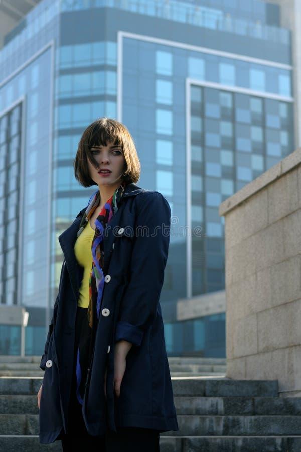 Affärskvinna i formell kläder mot den stads- bakgrunden royaltyfri bild