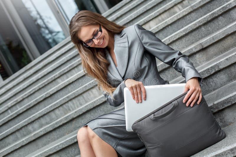 Affärskvinna i glasögon som sitter på trappa på stadsgatan som sätter bärbara datorn in i glat för fall som göras med arbete fotografering för bildbyråer