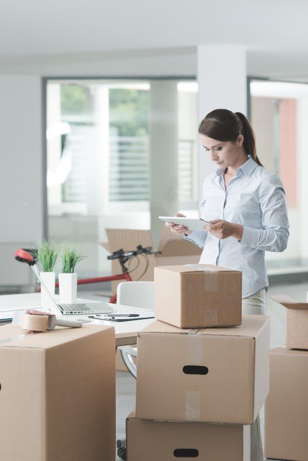 Affärskvinna i hennes nya kontor genom att använda en minnestavla arkivbilder