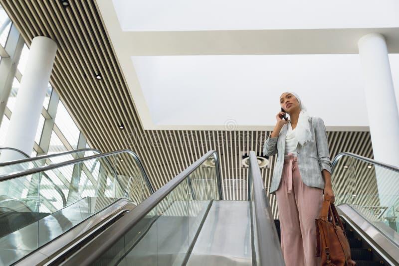 Affärskvinna i hijab med handväskan som talar på mobiltelefonen på rulltrappan i ett modernt kontor arkivbilder