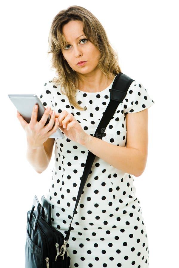 Affärskvinna i pricks klänning genom att använda minnestavlan arkivfoton