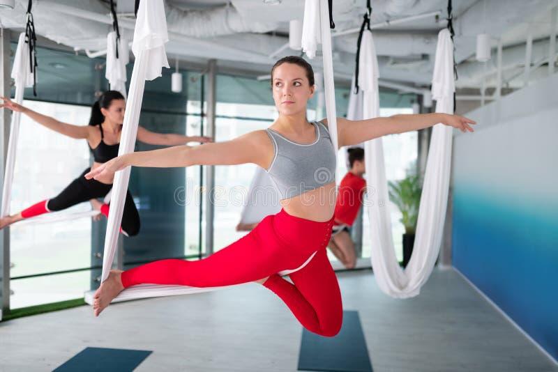 Affärskvinna i röd damasker som deltar i flyg- yogakurs fotografering för bildbyråer