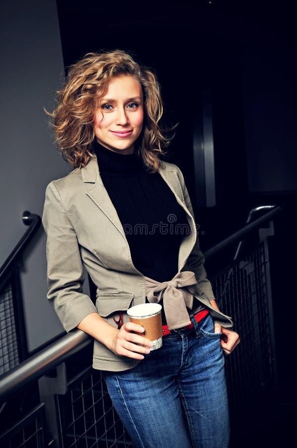 Affärskvinna i regeringsställning med kaffe arkivfoto