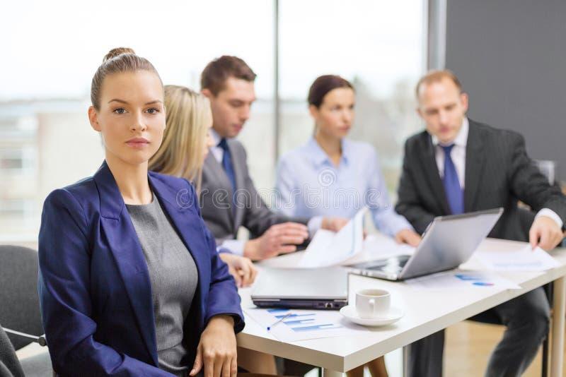 Download Affärskvinna I Regeringsställning Med Laget På Baksidan Fotografering för Bildbyråer - Bild av kontor, tygeln: 37345691
