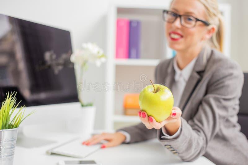 Affärskvinna i regeringsställning som rymmer äpplet arkivfoto