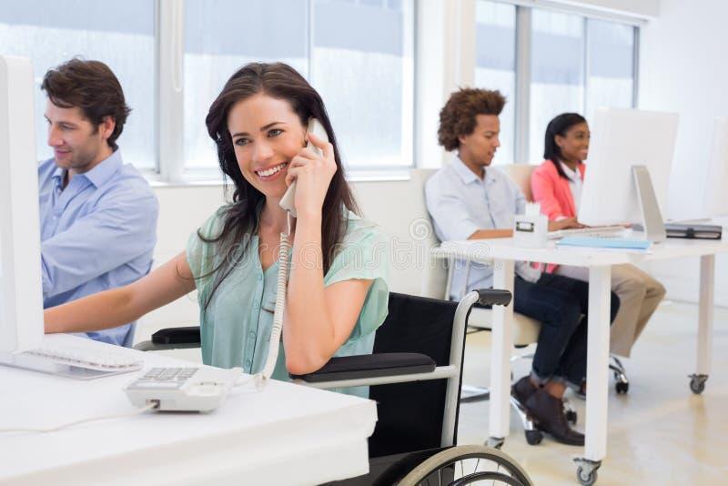 Affärskvinna i rullstol på telefonen arkivfoton
