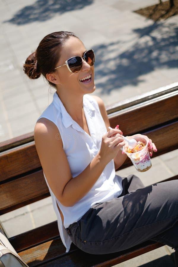 Affärskvinna i sleeveless skjorta som ler, medan äta som är sunt fotografering för bildbyråer