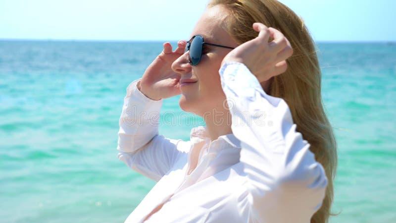Affärskvinna i solglasögon på stranden Hon jublar i havet och solen Hon knäppte upp hennes skjorta och andas in royaltyfria bilder