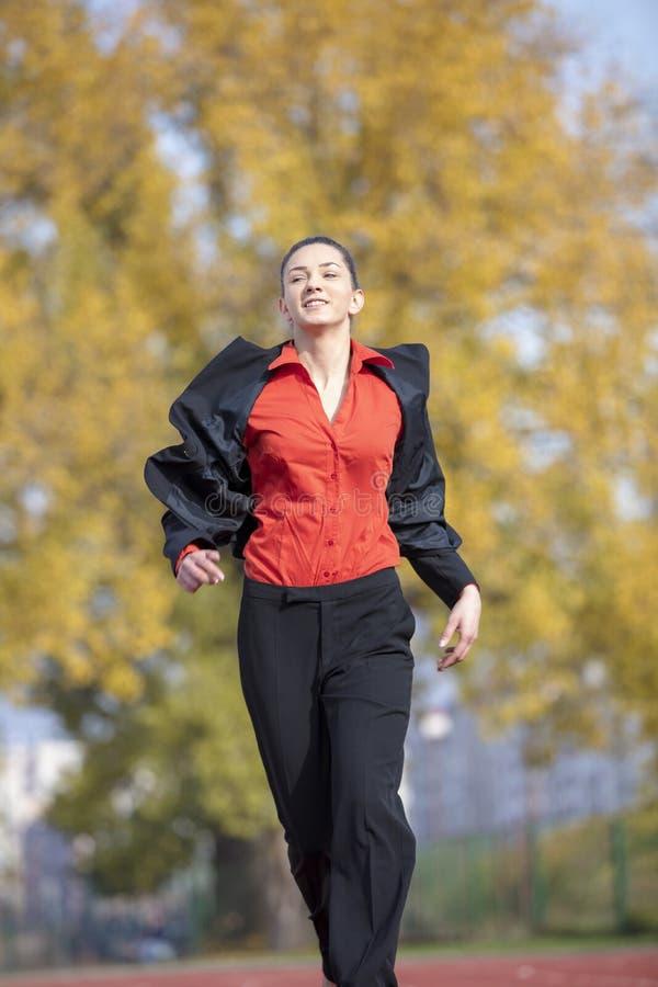 Affärskvinna i startpositionen som är klar att köra och sprinta på tävlings- spår för friidrott arkivbilder