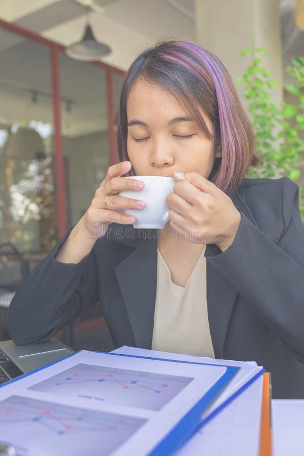 Affärskvinna i svart dräkt som tycker om koppen kaffe arkivbild
