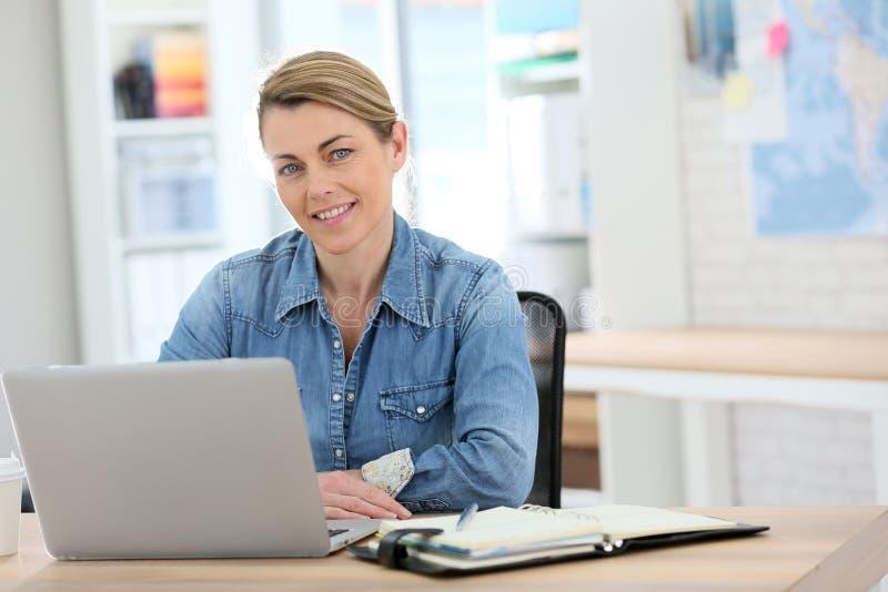 Affärskvinna i tillfällig kläder som arbetar på bärbara datorn royaltyfri foto