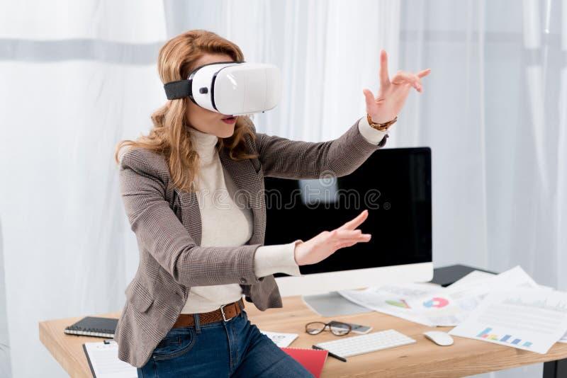 affärskvinna i virtuell verklighethörlurar med mikrofon på arbetsplatsen royaltyfri bild