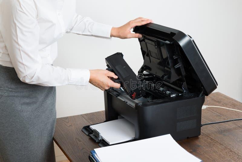 Affärskvinna Inserting Laser Cartridge i skrivare royaltyfria foton