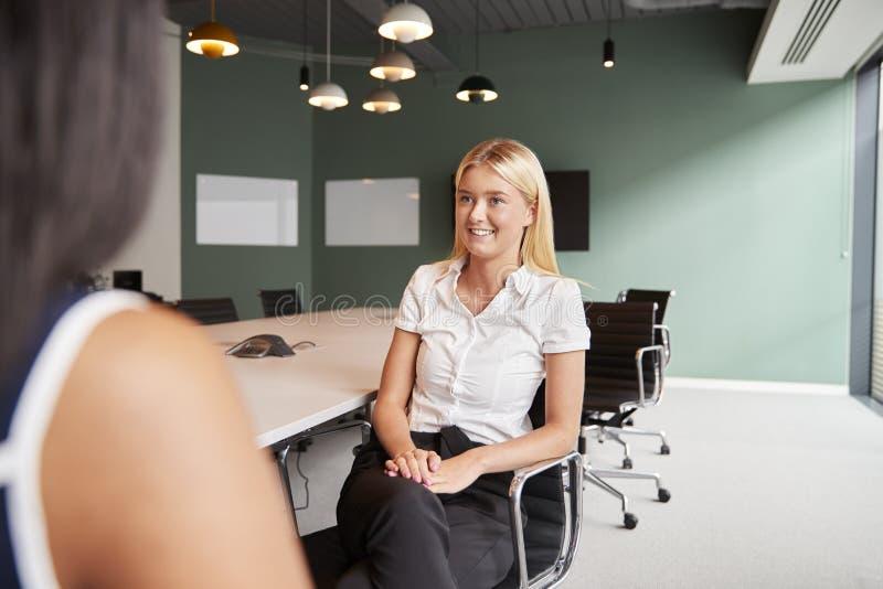 Affärskvinna Interviewing Female Candidate på den doktorand- rekryteringbedömningdagen i regeringsställning royaltyfria bilder