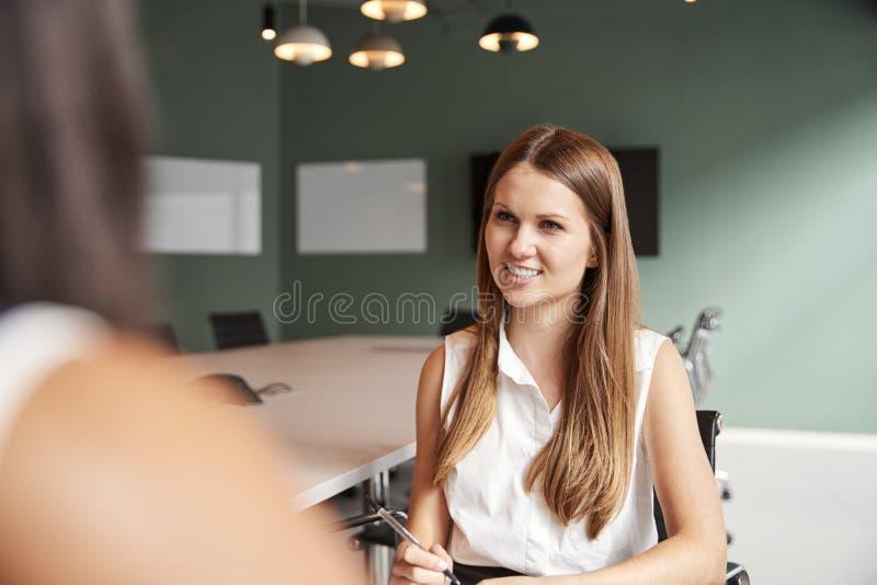 Affärskvinna Interviewing Female Candidate på den doktorand- rekryteringbedömningdagen i regeringsställning arkivbild