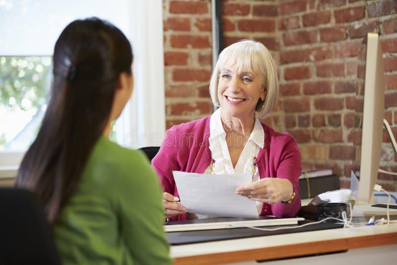 Affärskvinna Interviewing Female Job Applicant In Office royaltyfri bild
