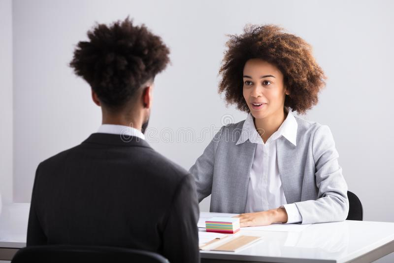 Affärskvinna Interviewing Male Applicant royaltyfria foton