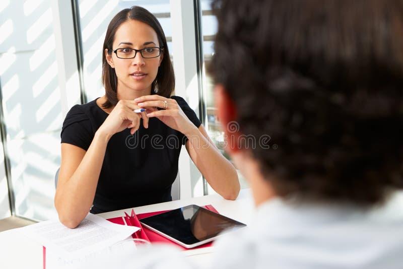 Affärskvinna Interviewing Male Candidate arkivfoto