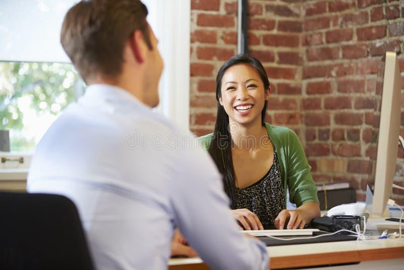 Affärskvinna Interviewing Male Job Applicant In Office royaltyfria bilder