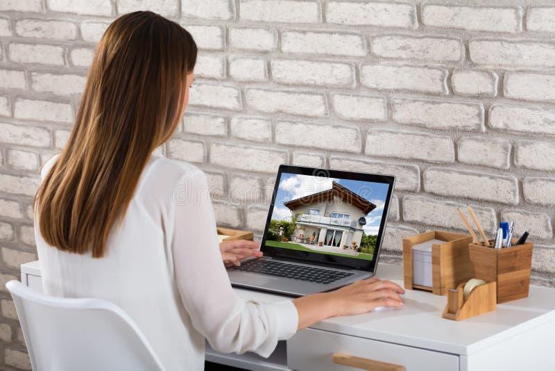 Affärskvinna Looking At House på bärbara datorn royaltyfria foton