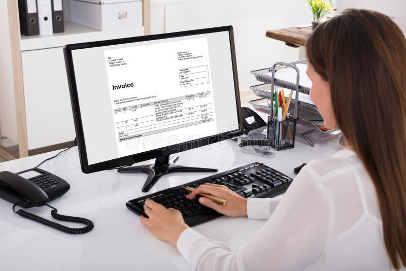 Affärskvinna Looking At Invoice på datoren arkivfoton