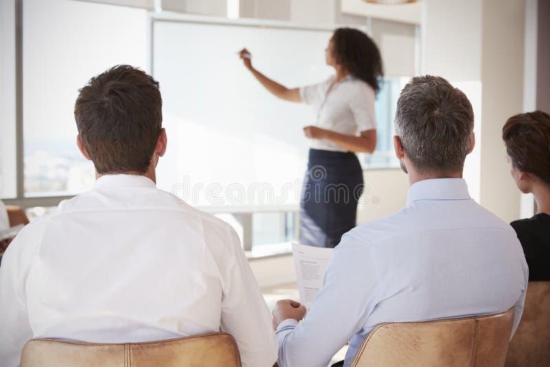 Affärskvinna Making Presentation Shot till och med dörröppningen arkivbild