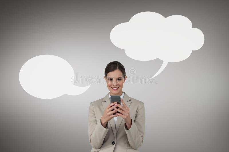 Affärskvinna med anförandebubblan genom att använda en telefon mot grå bakgrund royaltyfria bilder