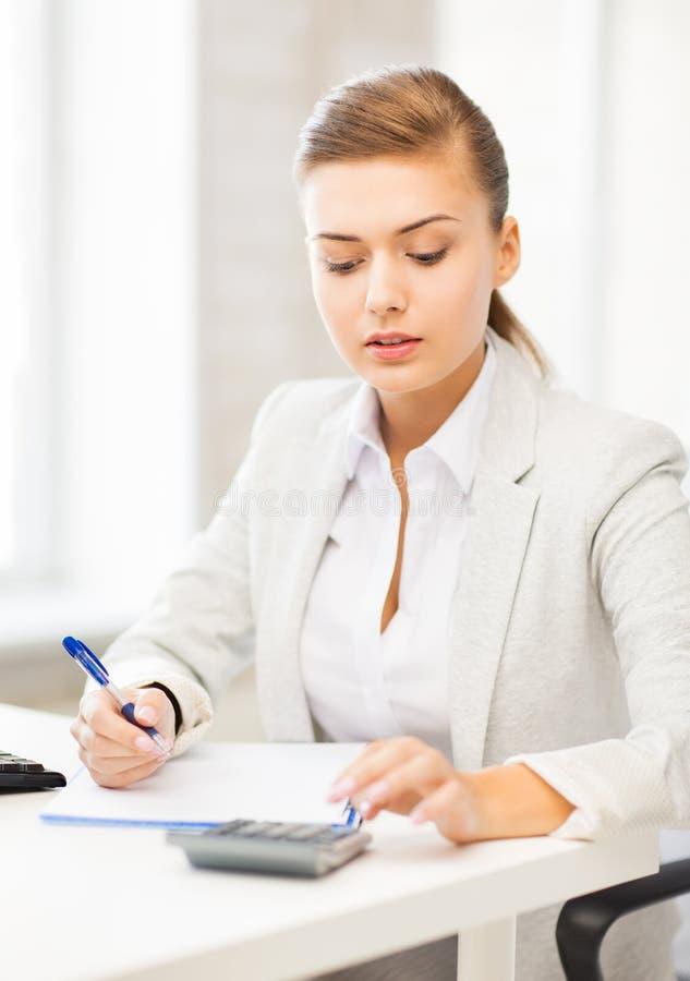 Affärskvinna med anteckningsboken och räknemaskinen royaltyfri foto